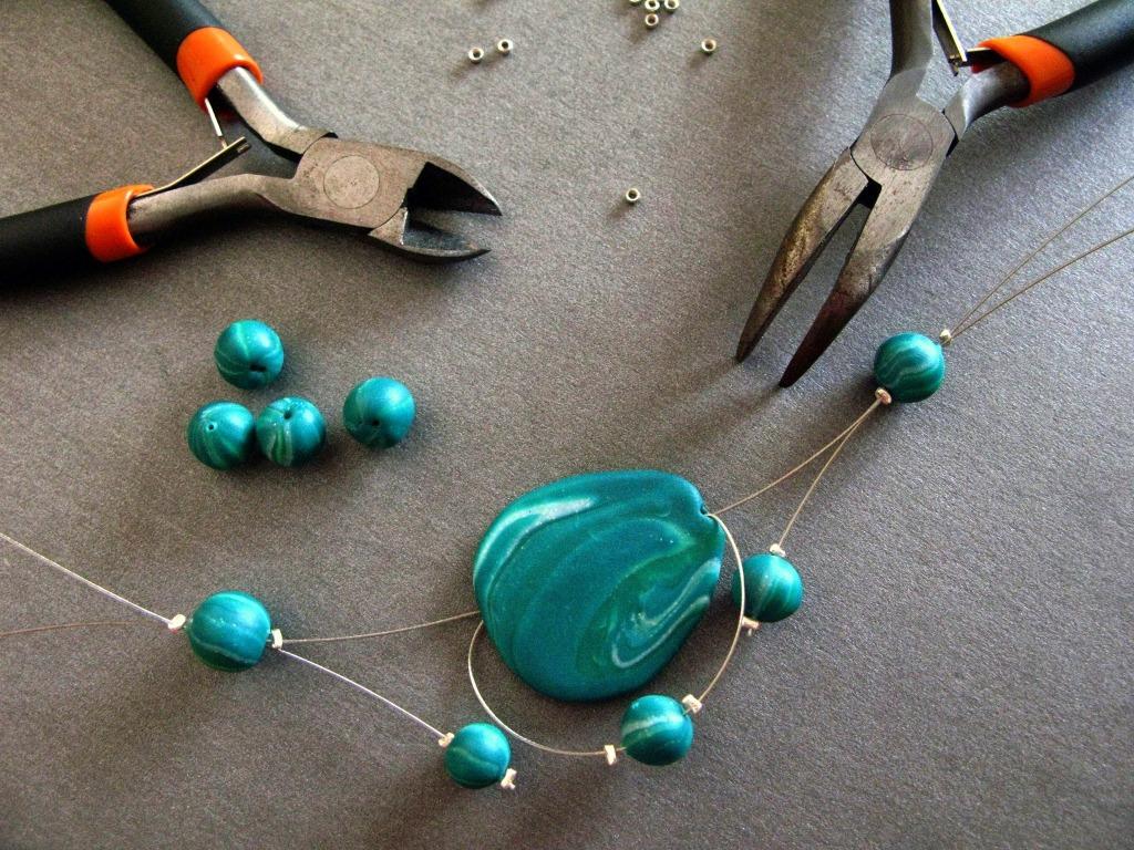 Sertissage des perles sur le fil acier gainé